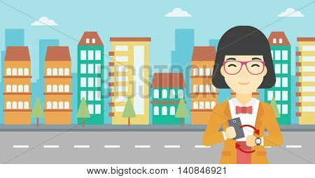 An asian young woman holding a smartphone looking at her smart watch. Concept of synchronization between smartwatch and smartphone. Vector flat design illustration. Horizontal layout.