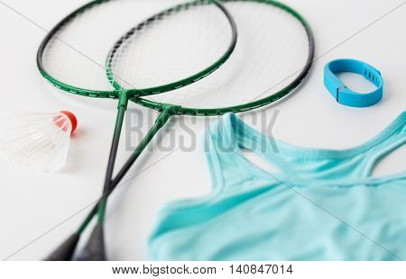 sport, healthy lifestyle and objects concept - close up of badminton rackets with shuttlecock, fitness tracker and sports top