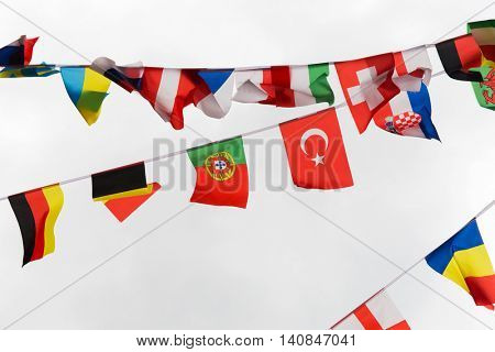 international symbolics and unity concept - close up of national flags garland decoration