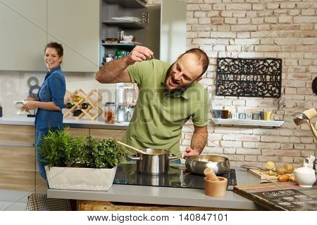 Young couple cooking together in kitchen, man tasting spaghetti.