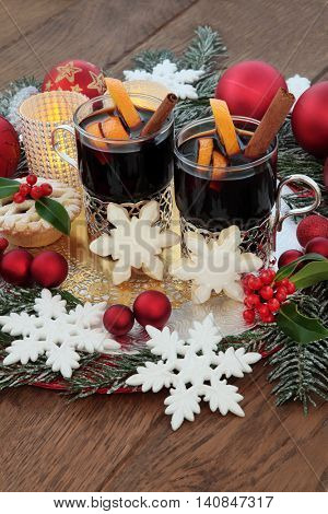 Christmas mulled wine, gingerbread biscuits, snowflake and red bauble decorations, candles, holly and snow covered fir over oak background.