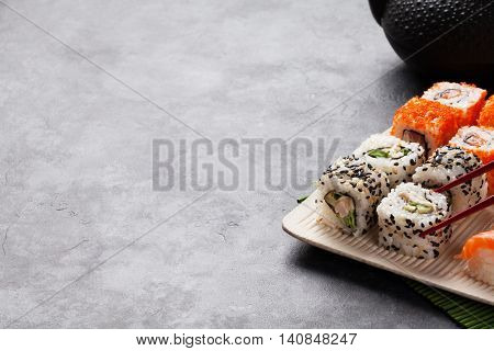 Set of sushi maki and green tea on stone table. View with copy space