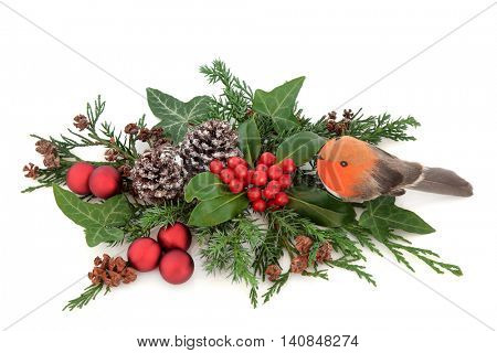 Christmas floral decoration with robin and red bauble decorations, holly, ivy, pine cones, cedar cypress and fir over white background.