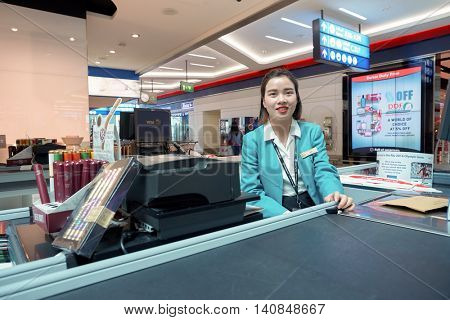 DUBAI, UAE - MAY 13, 2016: indoor portrait of a cashier at Dubai International Airport. Dubai International Airport is the primary airport serving Dubai, United Arab Emirates.