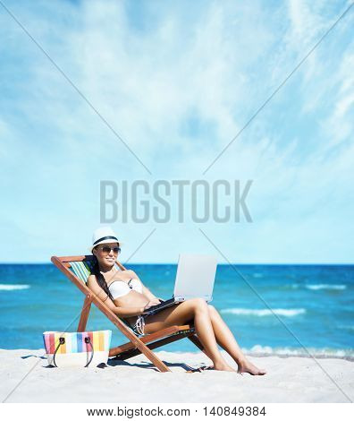 Gorgeous, sexy, smiling girl lying on a sunbed and working with laptop on the beach.