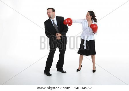 Woman with boxing gloves punching  a businessman