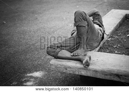A Man lying on the concrete bench