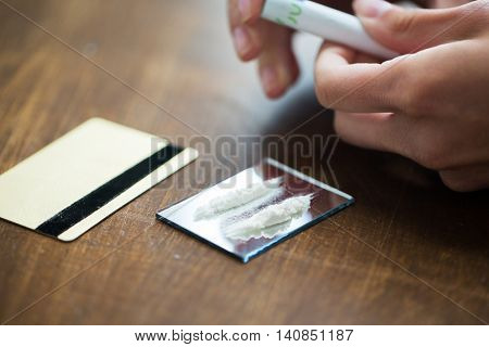 drug use, people, addiction and substance abuse concept - close up of addict hands with crack cocaine drug dose track on mirror, credit card and money roll