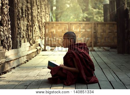 Novice monk learning reading book in the temple mandalayMyanmar