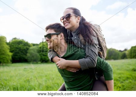 travel, hiking, backpacking, tourism and people concept - happy couple in sunglasses with backpacks having fun and walking along country road outdoors