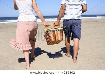 Pareja con cesta de picnic en la playa