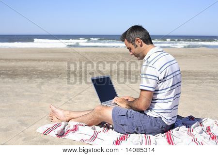 Man using a laptop at beach