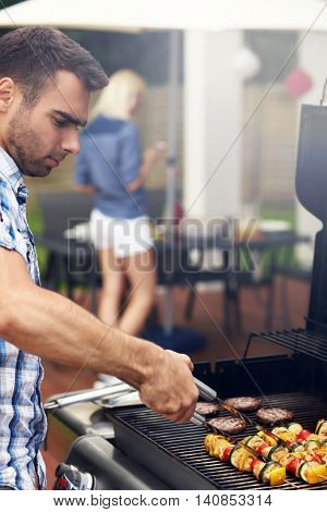 Picture of young man grilling food