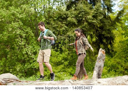 travel, hiking, backpacking, tourism and people concept - happy couple with backpacks walking along fallen tree trunk outdoors