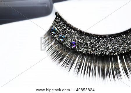Black false eyelash with rhinestone on white background