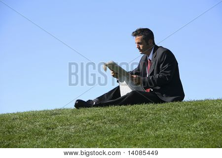 Businessman sitting outdoors reading newspaper