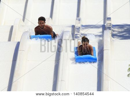 Rhodes Greece-July 15 2016:Young happy couple on the mat racer slide.Mat racer slide is very popular for young people in the Water Park. Water Park is located on the island of Rhodes in Greece and one of the most largest in Europe