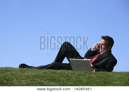 Businessman outdoors talking on cell phone and working on laptop computer