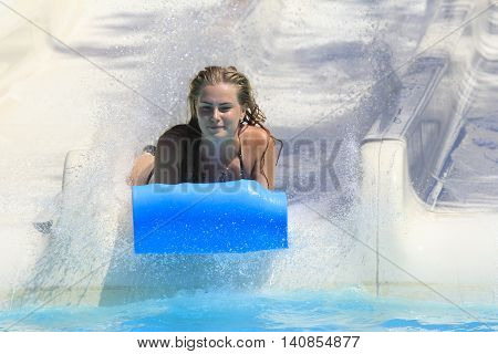 Rhodes Greece-July 15 2016:Young girl on the mat racer slide.Mat racer slide is very popular for young people in the Water Park.Water Park is located on the island of Rhodes in Greece and one of the most largest in Europe and is a very popular