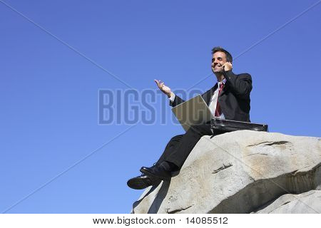 Kaufmann sitting on Top of Rock mit Laptop und Handy