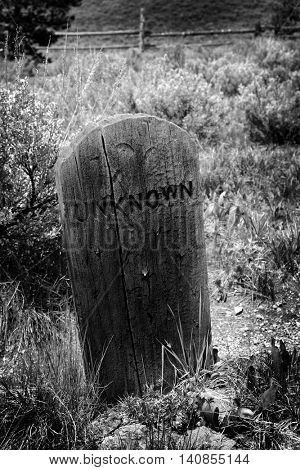 Gravestone in graveyard with unknown headstone