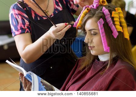 Process of hair style making. Hair dressing. Hair curlers. Business style