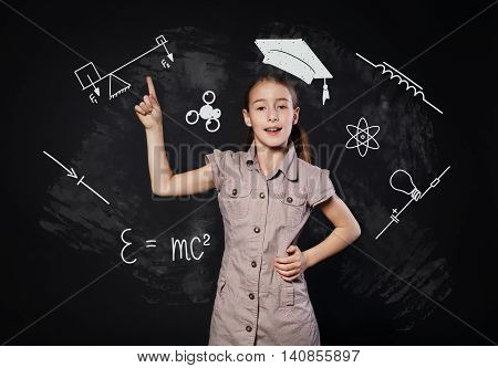 Small girl in imaginary graduation cap has an idea. Child shows finger up as eureka sign. Smart schoolgirl studio portrait near chalkboard with education icons. Studying science concept.