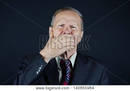 Business Man with hand closing his mouth isolated on black background