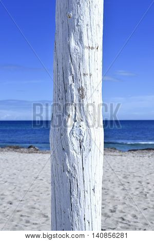 white flagpole on the beach. selective focus of a white pole on a sunny beach with blue sky and white sand.