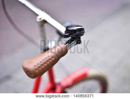 Red vintage bicycle with selective focus on the handlebar and bicycle bell. Macro shot with copy space.