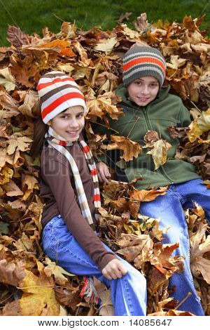 Young boy and girl sitting in pile of leaves