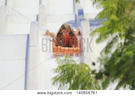 Rhodes Greece-July 25 2016:Young happy girl on the mat racer slide.Mat racer slide is very popular for young people in the Water Park. Water Park is located on the island of Rhodes in Greece and one of the most largest in Europe