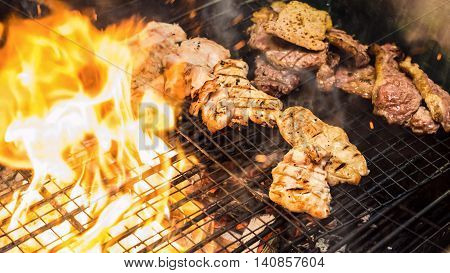 Assorted delicious grilled meat over the flame on a barbecue
