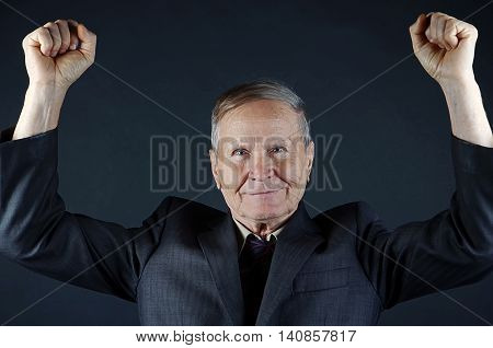 Happy Caucasian businessman on black background, two fists up.senior man closeup portrait isolated on black background. Emotions, facial expression and people concept