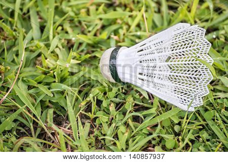Badminton shuttlecock with plastic feathers on green grass