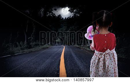 Back view of young girl is standing on a country road in a forest. Lonely child with doll sad gesture. Negative human emotion. Outdoors. The moon were NOT furnished by NASA.