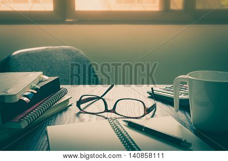 Glasses put down on table beside notebooks and pen in morning time on work day. Business working at home concept with vintage filter effect