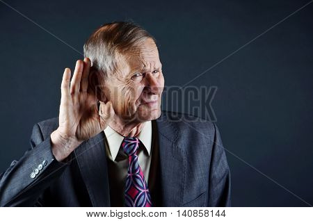 Businessman holding hand near his ear . Deaf businessman trying to listen, senior man closeup portrait isolated on black background. Emotions, facial expression and people concep