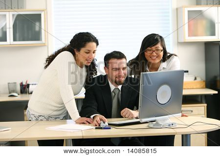 Three business people looking at computer