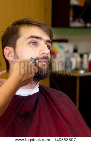 Young man in hair cutting salon. Mustache. New look