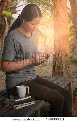 Young woman using her smartphone seriously while sitting in outdoor park on wood table in morning time on weekend. Freelance business working and phone addiction concept