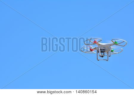 View on flying quadrocopter in clear blue sky in sunlight.Isolated.
