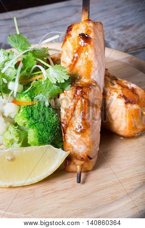 Salmon skewer with soy sauce served on wooden board