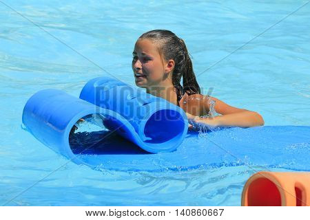 Rhodes Greece-July 29 2016: The young girl in the pool after mat racer slide in Water park.Mat racer slide is very popular for young people in the Water Park. Water Park is located on the island of Rhodes in Greece and one of the largest