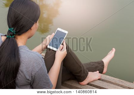 Weekend morning lifestyle. Young woman using her mobile phone seriously while sitting outdoor beside river in morning time. Freelance working and phone addiction concept