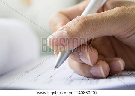 hand with pen over application form, completing maintenance information on a form