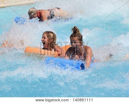 Rhodes Greece-July 29 2016: Two young girl on the mat racer slide in Water park.Mat racer slide is very popular for young people in the Water Park.Water Water Park is located  on the island of Rhodes in Greece and one of the largest in Europe
