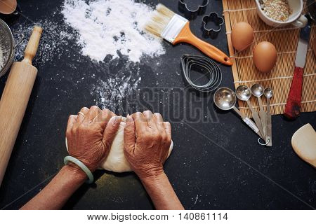 Hands of woman kneading dough, view from above