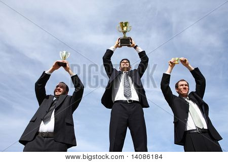 Three businessmen holding up trophies