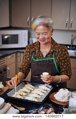 Smiling VIetnamese woman cooking croissants in the morning